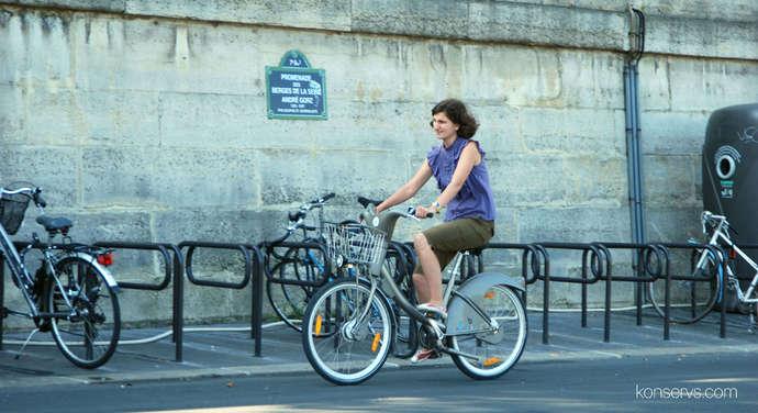 Консерва едет на Velib по набережной Сены